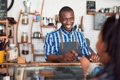 Barista sorridente che prende una carta di credito da un cliente del caffè Fotografia Stock