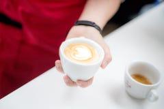 Barista sostiene una taza con un latte figurado del café bajo la forma de corazón foto de archivo libre de regalías
