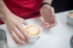 Barista sostiene una taza con un latte figurado del café bajo la forma de manzana Manos imagen de archivo libre de regalías