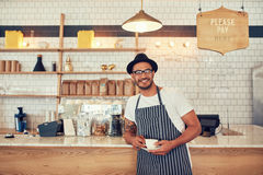 Barista standing at bar counter and smiling at camera. Portrait of a handsome young man standing at the counter of his cafe, he is wearing an apron and hat Stock Images