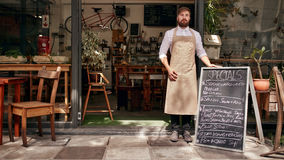 Barista standing in the doorway of a restaurant. Portrait of young man standing at the entrance of his coffee shop with a black board. Barista standing in the stock photo