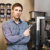 Barista standing with wrench near coffee maker Stock Photography