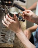 Barista Steaming Milk In Coffeeshop Foto de archivo