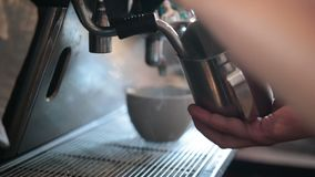 Barista steaming milk to prepare cappuccino stock footage