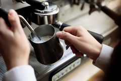 Barista steaming milk using modern coffee machine. Closeup royalty free stock photo