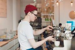Barista steht hinter der Kaffeemaschine und macht Kaffee stockbild