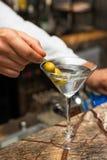 Barista sul lavoro, preparante i cocktail Preparazione del martini con le olive Fotografia Stock