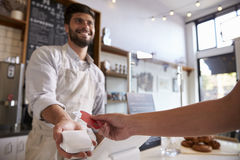Barista takes credit card payment at a coffee shop, close up Stock Photography