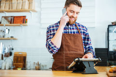 Barista taking order on cellphone and using tablet in cafeteria Royalty Free Stock Photo