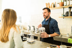 Barista talking about coffee grains. Portrait of a handsome young barista talking about coffee grains and brewing process to a customer in a cafe royalty free stock image