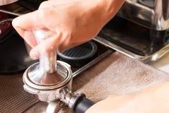 Barista Tamping Espresso Grounds Stockfotografie