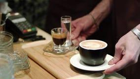 Barista tar kaffe från räknarecappuccinot, och esprresoy bär kunder till besökare till ett kafé stock video