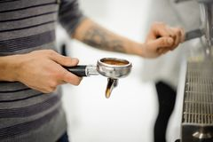 Barista with tattoo holding a temper with coffee Stock Images