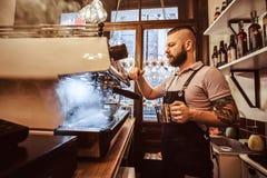 Barista tatuato con funzionamento alla moda dell'acconciatura e della barba su una macchina del caffè in una caffetteria o in un  fotografia stock libera da diritti