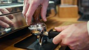 Barista trycker på jordkaffe i ett kafé shoppar och gör kaffe genom att använda maskinen stock video