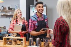 Barista-Umhüllungskunde geben Lohnliste der Karte am Kaffeestubebarzähler Lizenzfreies Stockfoto