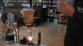 Barista usando - fabricante de café del sifón - un fabricante de café del vacío que prepara el café almacen de metraje de vídeo
