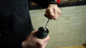 barista uses a manual coffee grinder to grind coffee beans