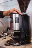 Barista using coffee grinder to grind beans Royalty Free Stock Photos