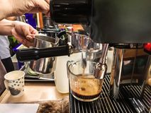 Barista using coffee machine automatic preparing fresh coffee or cappuccino and pouring into glass cup. Stock Image