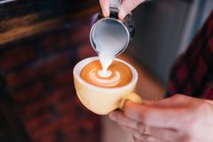 Barista using coffee machine preparing fresh coffee with latte foam at coffee shop and restaurant, bar or bistro Stock Image