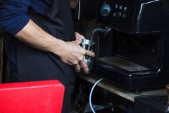 Barista using coffee machine to Steaming milk froth for preparing coffee. stock photography