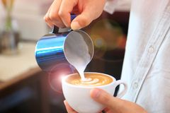Barista using pitcher for pouring frothed milk to cup of coffee latte tulip pattern on top stock image