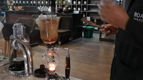 Barista using - syphon coffee maker - a vacuum coffee maker that brews coffee. Using two chambers where vapor pressure and vacuum produce coffee stock video footage