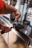 Barista using a tamper to press ground coffee Royalty Free Stock Photography