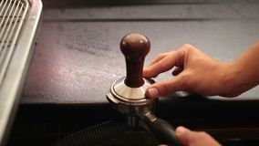 Barista using a tamper to press ground coffee stock footage