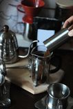 Barista vierte el café molido de la amoladora de café en la prensa del francés Paquete con la etiqueta blanca Imagen de archivo libre de regalías