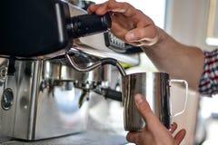 Barista wärmt die Milch auf Stockfoto