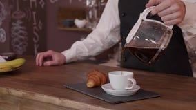 Barista wolny nalewa filiżanka kawy słuzyć z croissant zbiory