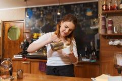 Barista woman pouring cream to cup at coffee shop Stock Photos