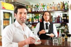 Barista z klientem w jego kawiarni lub coffeeshop Zdjęcie Stock