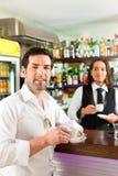 Barista z klientem w jego kawiarni lub coffeeshop Zdjęcia Stock