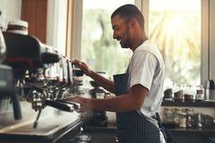 Baristaen gör cappuccino i kafé arkivbilder
