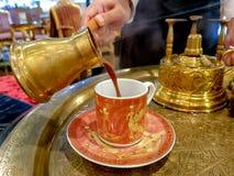 Baristaen häller av kaffe för egyptisk stil för förmögenhetkassören svart från mässingskruset in i den tomma koppen royaltyfria foton