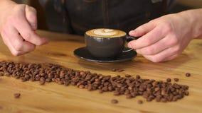 Baristamens die een kop van cappuccino met een patroon op het schuim op de lijst zetten stock footage