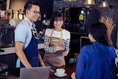 Baristas asiáticos jovenes que ordenan en la barra contraria en café Resta del café Imagenes de archivo