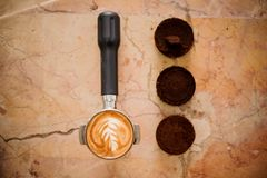 Baristas temper with latte art and three coffee tablets Royalty Free Stock Photo
