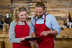 Baristas using digital tablet in coffee shop. Male and female baristas using digital tablet in coffee shop Royalty Free Stock Photography
