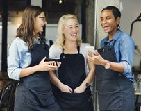 Baristas watching something funny on a phone royalty free stock photo