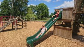Wood chippings and children sliding down a green slide. Bark child boy girl sitting on slide in background focus ground relaxing jungle gym sliding climbing stock photography