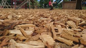 Close up of wood chippings on a playground floor. Bark child sitting on slide in background focus ground relaxing jungle gym climbing frame swings boy in red t royalty free stock image