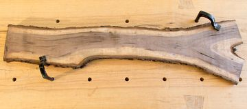 Bark edge walnut board on workbench Royalty Free Stock Photos