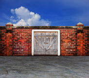 Bark panel  wood barn door on old brick wall with blue sky behin Stock Photo