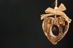 Bark wooden heart on a rope with little opaque brass bell in the Royalty Free Stock Photos