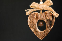 Bark wooden heart on a rope with little opaque brass bell in the Stock Photos