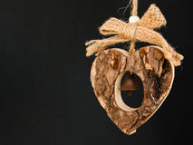 Bark wooden heart on a rope with little opaque brass bell in the Royalty Free Stock Images